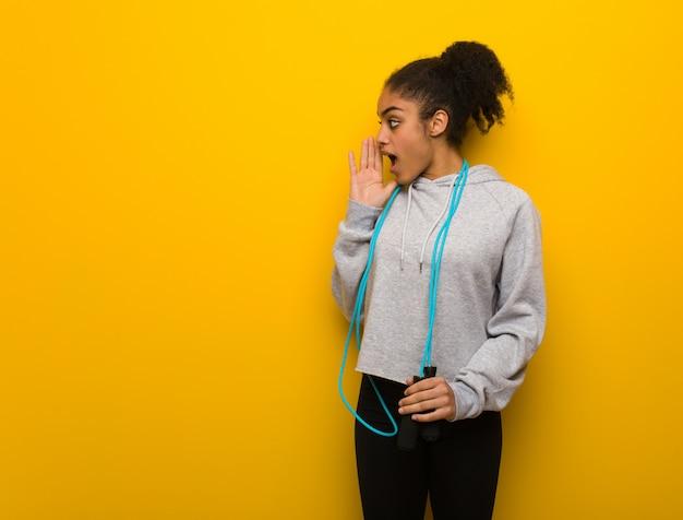 Młoda kobieta czarny fitness szepcząc plotek półgłosem. trzymając skakankę.