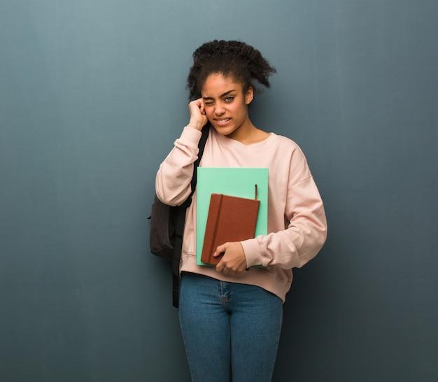 Młoda kobieta czarny student obejmujące uszy rękami. trzyma książki.