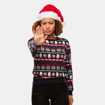 Młoda kobieta czarny w modny sweter christmas z nadrukiem kładzenie ręki z przodu