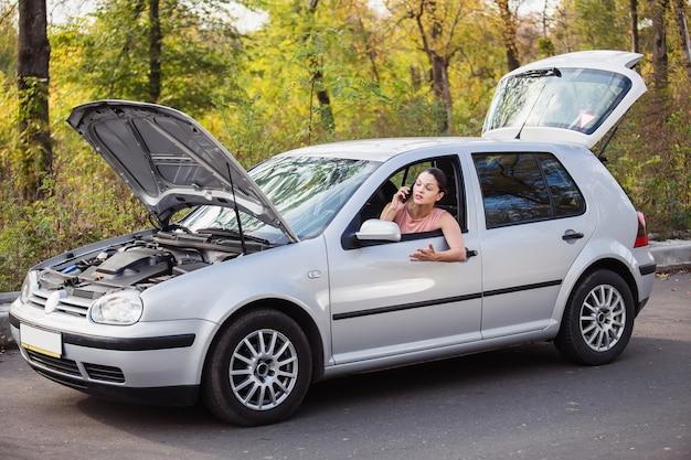 Młoda kobieta czeka na pomoc w pobliżu samochodu, który zepsuł się na poboczu drogi