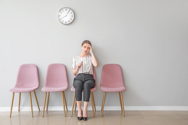 Młoda kobieta czeka na rozmowę kwalifikacyjną w pomieszczeniu