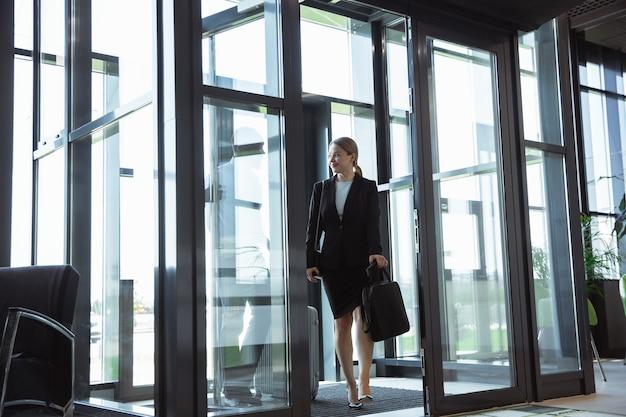 Młoda kobieta czeka na wyjazd na lotnisko, podróż służbowa, biznesowy styl życia.