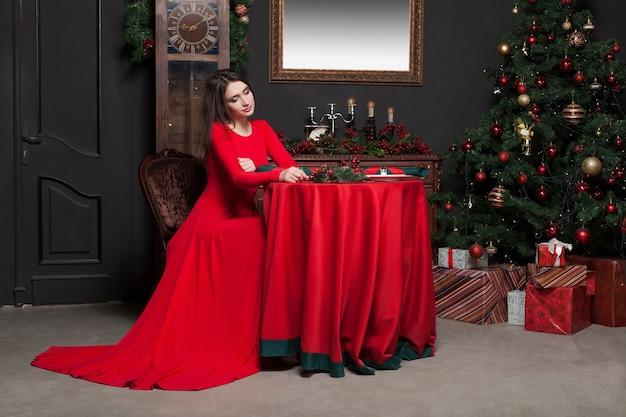 Młoda kobieta czeka w restauracji vintage. glamour kobieta w czerwonej sukience, romantyczny wieczór.