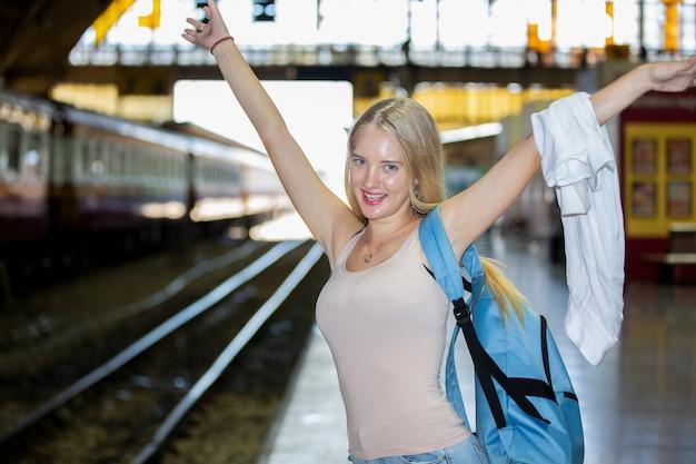 Młoda kobieta czeka w zabytkowym pociągu, zrelaksowana i beztroska na peronie w bangkoku w tajlandii przed złapaniem pociągu. fotografia podróżnicza. styl życia.