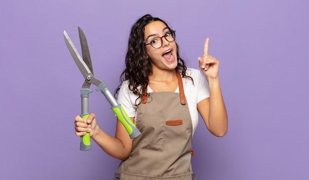 Młoda kobieta czująca się jak szczęśliwa i podekscytowana geniusz po zrealizowaniu pomysłu, radośnie podnosząca palec, eureka!