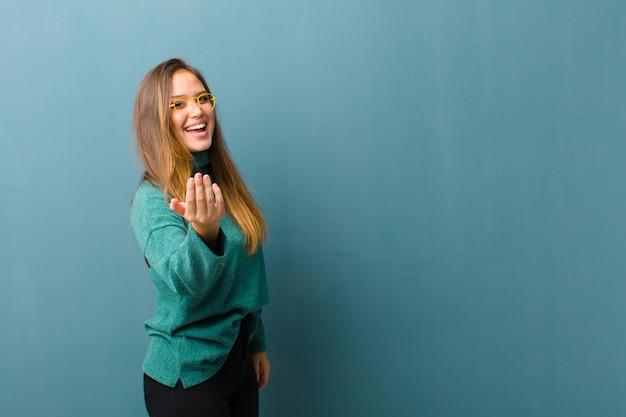Młoda kobieta czująca się szczęśliwa, odnosząca sukcesy i pewna siebie, stawiająca czoła wyzwaniu i mówiąca, że zacznij działać! lub witając cię