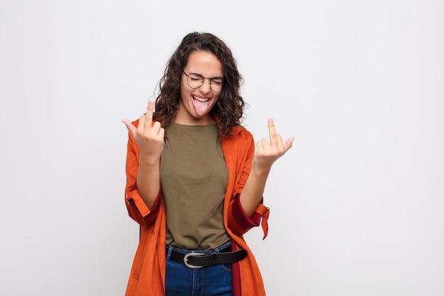Młoda kobieta czuje się prowokująca, agresywna i nieprzyzwoita, macha środkowym palcem, z buntowniczym nastawieniem na białej ścianie