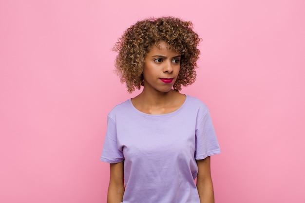 Młoda kobieta czuje się smutna, zdenerwowana lub wściekła i patrzy w bok z negatywnym nastawieniem, marszcząc brwi w sporze o różową ścianę