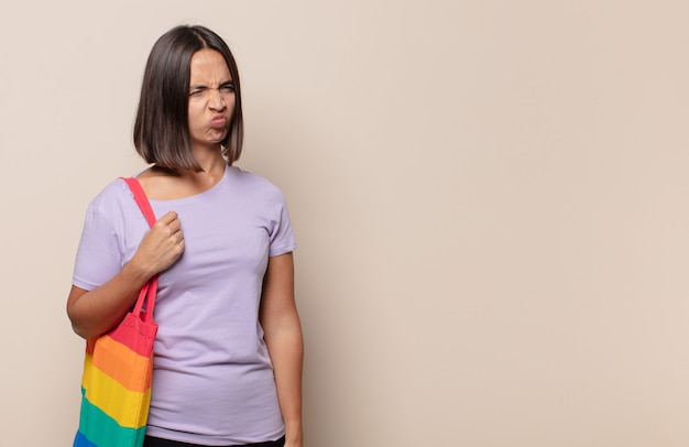 Młoda kobieta czuje się smutna, zdenerwowana lub zła i patrzy w bok z negatywnym nastawieniem, marszcząc brwi w niezgodzie