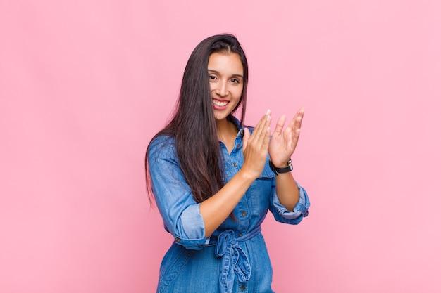 Młoda kobieta czuje się szczęśliwa i odnosi sukcesy, uśmiecha się i klaszcze w dłonie, gratuluje i brawa