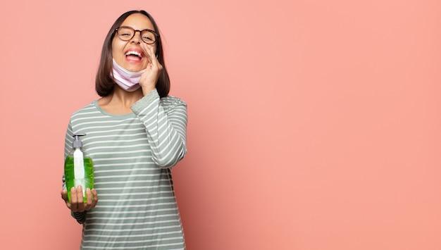 Młoda kobieta czuje się szczęśliwa, podekscytowana i pozytywna, wydając wielki okrzyk z rękami przy ustach, wołając