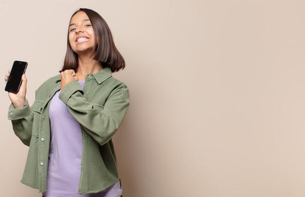Młoda kobieta czuje się szczęśliwa, pozytywna i odnosząca sukcesy, zmotywowana, gdy staje przed wyzwaniem lub świętuje dobre wyniki