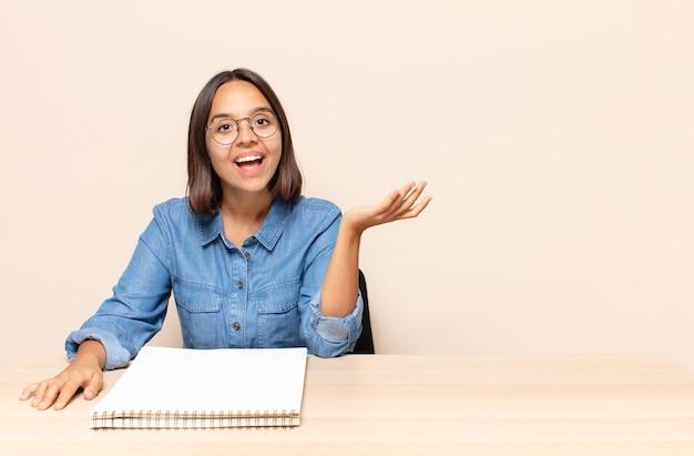 Młoda kobieta czuje się szczęśliwa, zaskoczona i pogodna, uśmiechnięta z pozytywnym nastawieniem, realizująca rozwiązanie lub pomysł