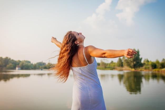 Młoda kobieta czuje się wolna i szczęśliwa, podnosząc ręce i kręcąc się wokół letniej rzeki