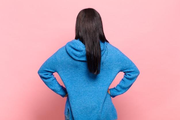 Młoda kobieta czuje się zdezorientowana lub pełna lub ma wątpliwości i pytania, zastanawia się, z rękami na biodrach, widok z tyłu