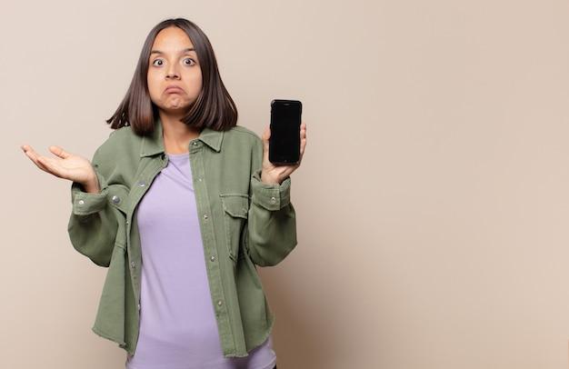 Młoda kobieta czuje się zdziwiona i zagubiona, wątpi, rozważa lub wybiera różne opcje z zabawnym wyrazem twarzy