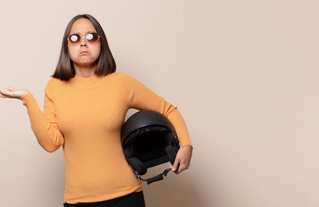 Młoda kobieta czuje się zdziwiona i zdezorientowana, wątpi, rozważa lub wybiera różne opcje z zabawnym wyrazem twarzy
