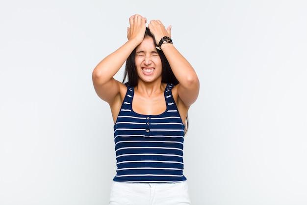 Młoda kobieta czuje się zestresowana i niespokojna, przygnębiona i sfrustrowana bólem głowy, podnosząc obie ręce do głowy
