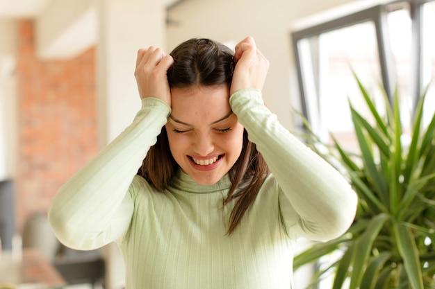 Młoda kobieta czuje się zestresowana i niespokojna, przygnębiona i sfrustrowana bólem głowy podnoszącym obie ręce do głowy