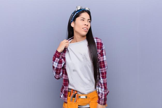 Młoda kobieta czuje się zestresowana, niespokojna, zmęczona i sfrustrowana, ciągnie szyję koszuli, wygląda na sfrustrowaną problemem