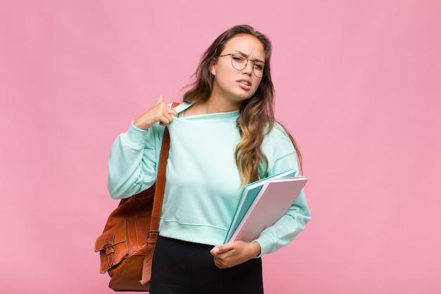 Młoda kobieta czuje się zestresowana, niespokojna, zmęczona i sfrustrowana, ciągnie za szyję koszuli, wygląda na sfrustrowaną problemem