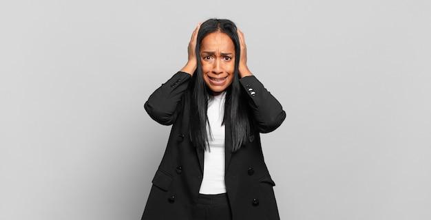 Młoda kobieta czuje się zestresowana, zmartwiona, niespokojna lub przestraszona, z rękami na głowie, panikująca z powodu błędu