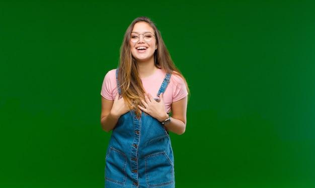 Młoda kobieta czuje sukces i jest zadowolona, uśmiechając się z szeroko otwartymi ustami, robiąc dobry znak ręką na zielono