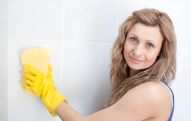 Młoda kobieta czyści łazienkę