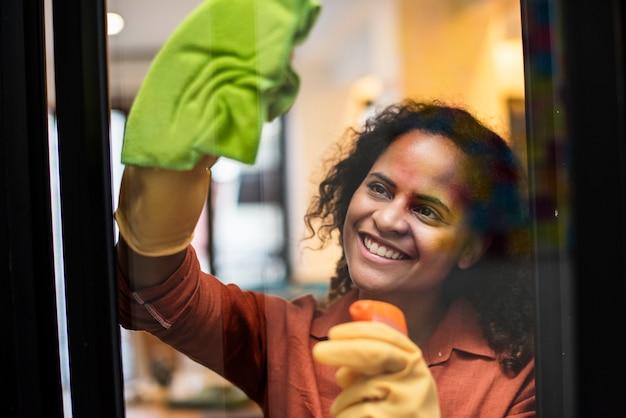 Młoda kobieta czyści okno