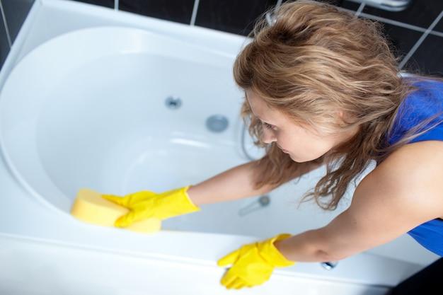 Młoda kobieta czyści skąpanie