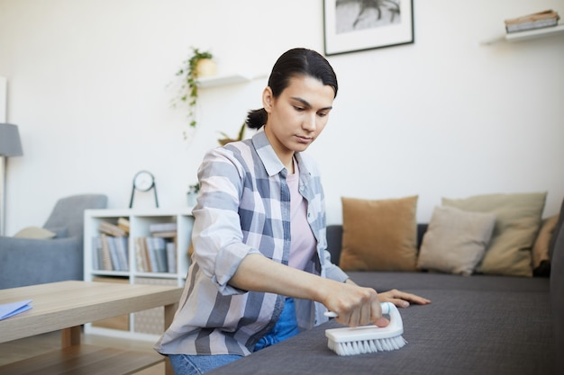 Młoda kobieta czyści sofę szczotką w salonie