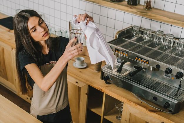 Młoda kobieta czyści szkło