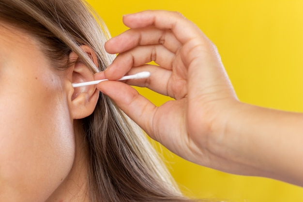 Młoda kobieta czyści ucho wacikiem na białym tle na żółtym tle