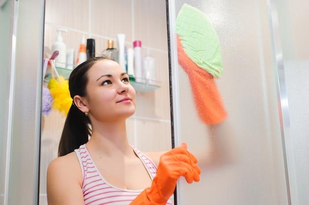 Młoda kobieta czyszczenia drzwi prysznicowe