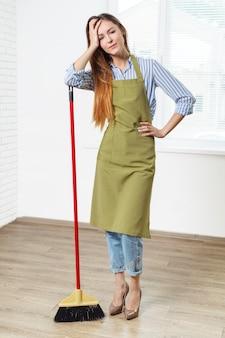 Młoda kobieta czyszczenia podłogi w pokoju