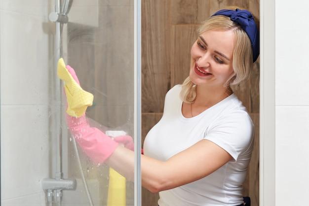 Młoda kobieta czyszczenia szklanej kabiny prysznicowej z gąbką i sprayem