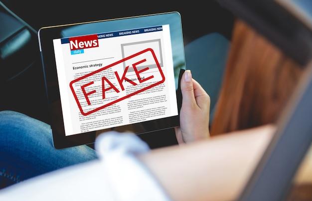Młoda kobieta czyta fałszywe wiadomości z tabletem w rękach siedząc w samochodzie