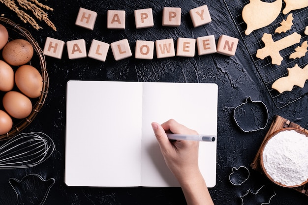 Młoda kobieta czyta i pisze przepis na robienie ciasteczek na halloween, koncepcja projektowania przygotowania do przyjęcia z okazji halloween, widok z góry, płasko świecki, narzut.