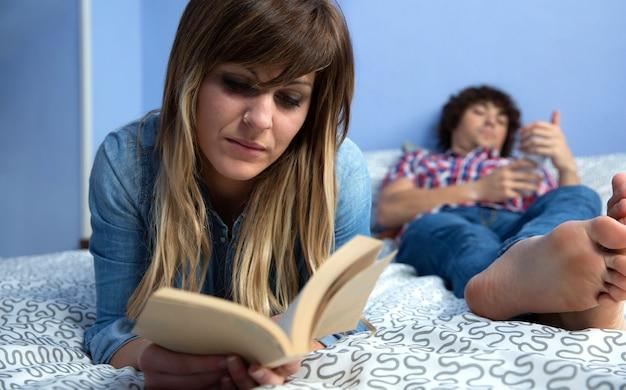 Młoda kobieta czyta książkę leżącą na łóżku, podczas gdy jej mąż patrzy na telefon komórkowy