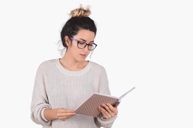 Młoda kobieta czyta książkę na bielu