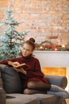 Młoda kobieta czyta książkę na kanapie