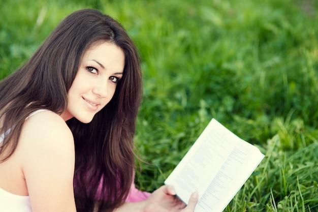 Młoda kobieta czyta książkę na łące
