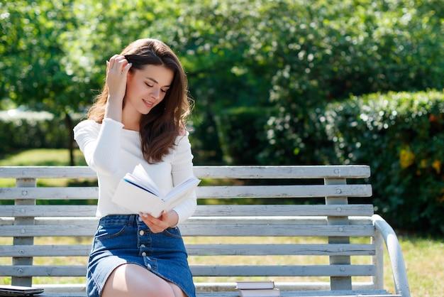 Młoda kobieta czyta książkę na ławce w parku