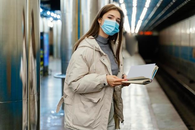 Młoda kobieta czyta książkę na stacji metra