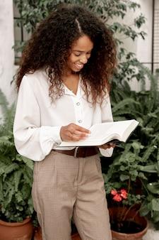 Młoda kobieta czyta książkę outside