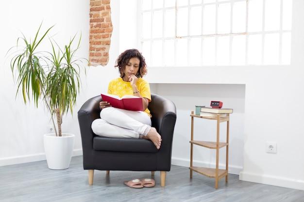 Młoda kobieta czyta książkę w domu. miejsce na tekst.