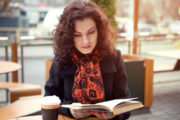 Młoda kobieta czyta książkę w kawiarni