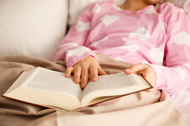 Młoda kobieta czyta książkę w łóżku w domu