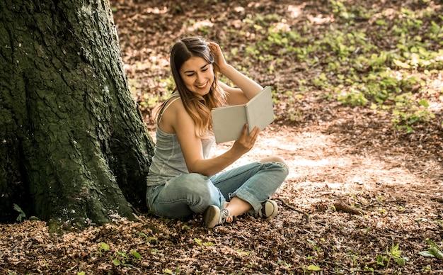 Młoda kobieta czyta książkę w pobliżu drzewa