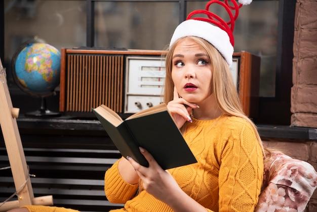 Młoda kobieta czyta książkę w santa kapeluszu.